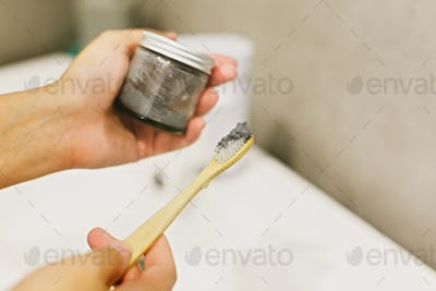 Woman using bamboo toothbrush and charcoal toothpaste from glass jar
