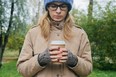 woman in autumnal casual clothes standing alone, looking down, holding in hands paper cup of coffee