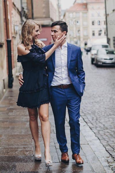 Portrait of stylish couple embracing in rainy european city street