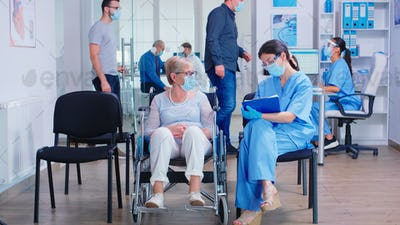 Nurse taking notes from disabled senier patient