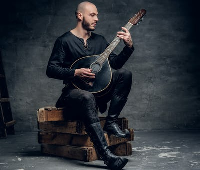 Traditional folk musician dressed in vintage Celtic clothes sits on a wooden box and plays mandolin.