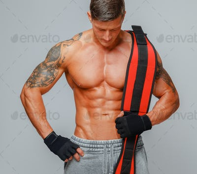 Strong muscular man poses showing his body and holding power belt on a shoulder.