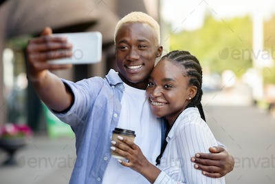 Happy african american millennial guy and girl with coffee, hugs and maks selfie