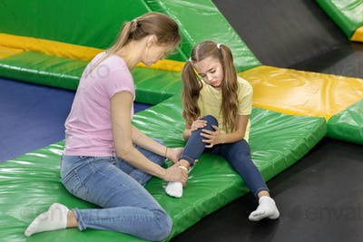 Trampoline jumping accident. Mom and child with foot injury sitting on rebounder at kids playground