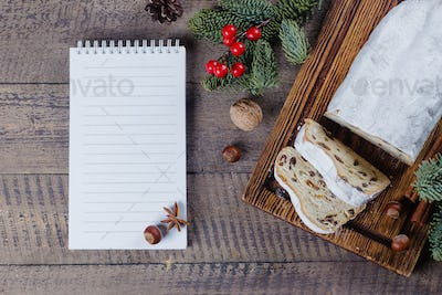 Traditional Christmas festive pastry dessert stollen with festive decoration and notebook white