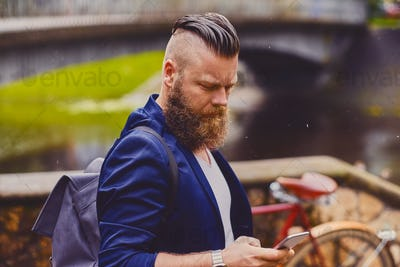 Bearded hipster male using smartphone in a park near river.