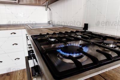 Burning gas from kitchen stove on background of stylish kitchen interior
