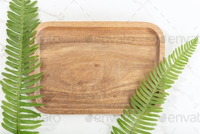 Flat lay of wooden tray and Green ivy leaves on white marble background