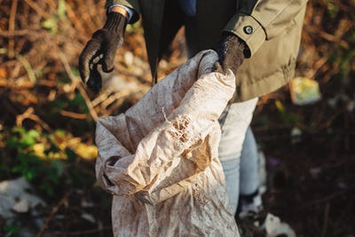 Woman hand in glove picking up trash, collecting garbage in bag