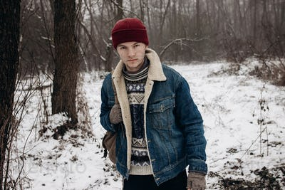 Stylish hipster traveler holding backpack, posing and smiling, in winter snowy forest