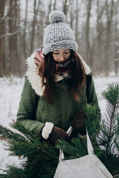 Иtylish hipster woman gathering and holding pine green branches in cloth bag