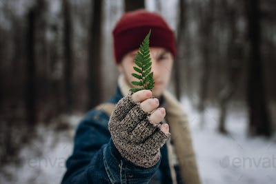 Stylish hipster traveler holding green leaf fern in front of face
