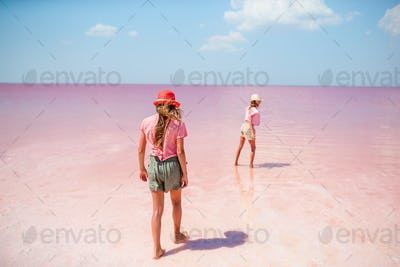 Girls on a pink salt lake on a sunny summer day