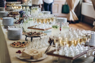 Stylish champagne glasses and food  appetizers on table at wedding reception