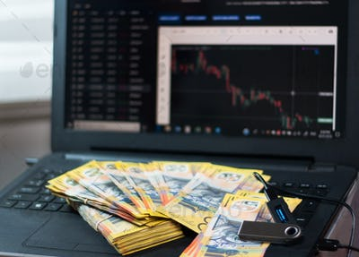 Australian dollars and nano wallet on the laptop with graphs and charts
