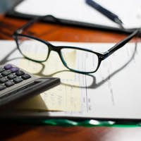 Glasses and calculator on a folder with documents, bills and notes on a desk