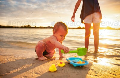 Baby playing with older sister on beach