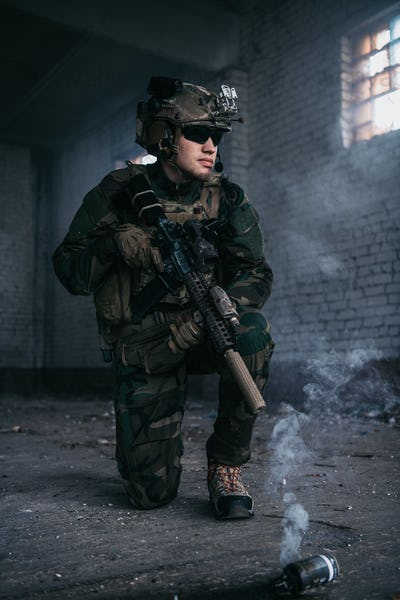 Military man during combat and smoke grenade on a ground