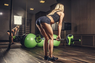 Female from the back doing exercises with green barbell.