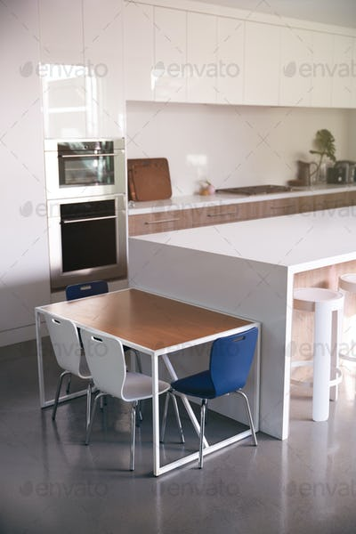 Interior View Of Beautiful Kitchen With Island Counter And Table For Children In New Family House