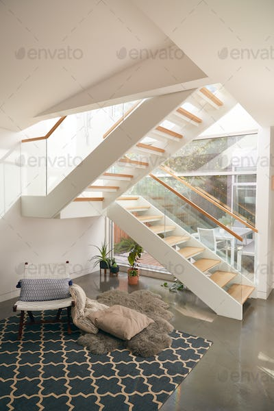 Interior View Of Beautiful Living Area With Glass Staircase And Soft Furnishings In New Family Home