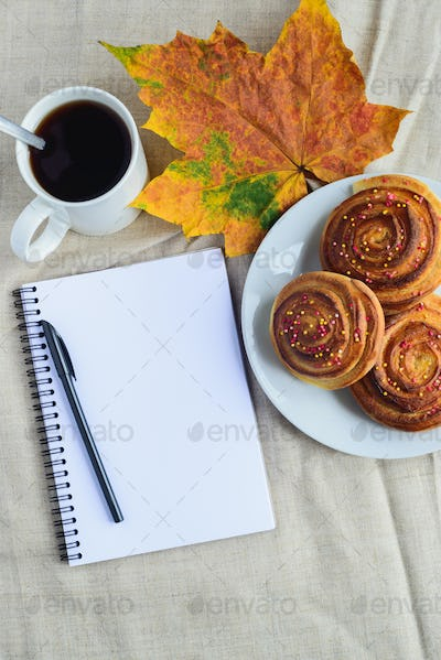 cinnamon rolls with topping on plate, cup of coffee, open notepad and pen, autumn leaf on table