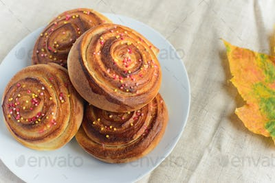 cinnamon rolls or buns with sugar sprinkle topping on white plate and autumn leaf on table
