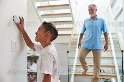 Grandfather With Grandson Adjusting Digital Central Heating Thermostat In Home