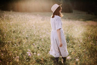 Boho woman relaxing in countryside flowers at sunset