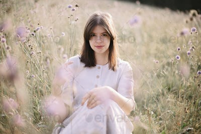 Stylish girl in rustic dress and hat sitting among wildflowers and herbs in sunny meadow