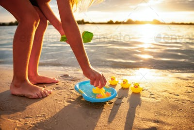 Unrecognizable kid playing with rubber duck toys on beach