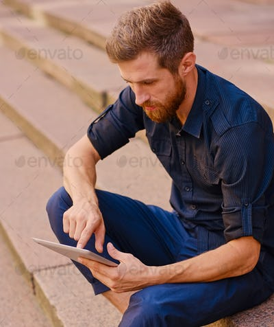 Bearded male sits on a step and using a tablet.