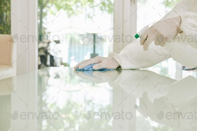 Worker in rubber gloves wiping surfaces