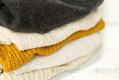 Cozy knitted sweater stack for cold autumn weather on white background