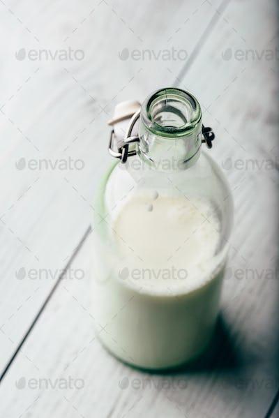 Almond milk in glass bottle on wooden surface