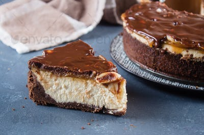 Slice of Cheesecake Snickers with chocolate, caramel, peanut paste, Nougat and Peanut Layered Cake