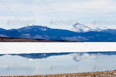 Snowy Mountains mirrored Lake Laberge Yukon Canada