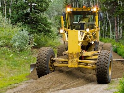 Grader resurfacing narrow rural road