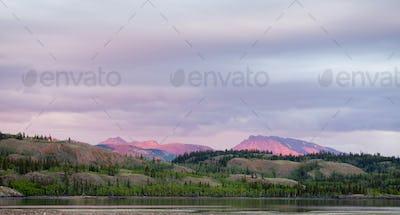 Distant mountains glow sunset light Yukon Canada