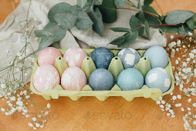 Natural dye easter eggs in carton tray on rustic table with flowers