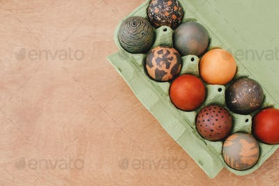 Stylish Easter eggs natural dye in carton tray on rustic table