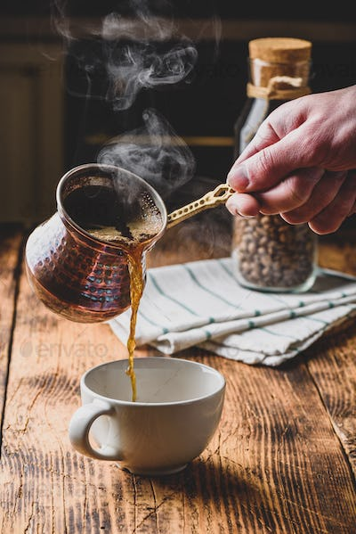 Pouring turkish coffee into white cup