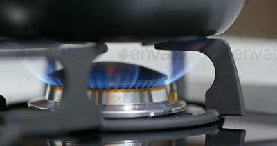 Stove top burner igniting into a blue for cooking