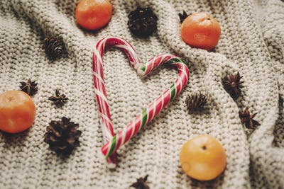 stylish peppermint candy cane in heart shape and pine cones and anise with tangerine