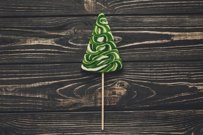 Christmas tree lollipop on rustic wooden background top view