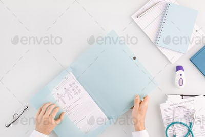 Hands of doctor opening folder with medical document while going to take it out