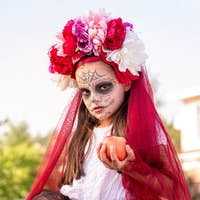 Young sullen girl with halloween paint on face and beautiful flowers on head