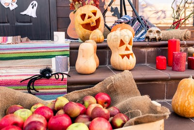 Group of ripe halloween pumpkins, spider, heap of apples, skull, red candles