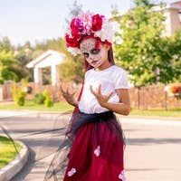 Schoolgirl with painted face in halloween costume looking with sulky expression