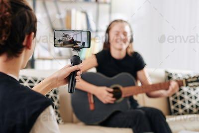 Boy filming sisnging friend